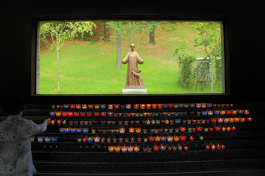聖母瑪利亞像前面拜訪了一些微弱燭光