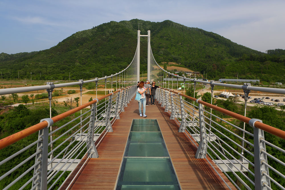 People are enjoying the open view of Hantangang River on the Sky Bridge. The scale of bridge is huge and the transparent glass part of the middle of bridge gives a thrill