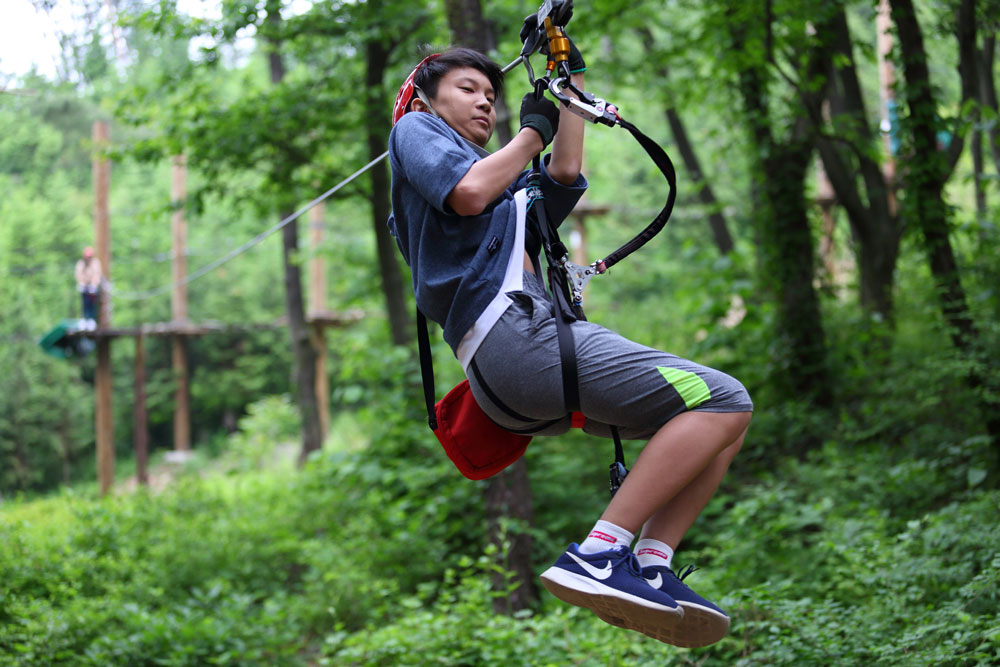 A side view of a boy riding Dynamic Eco Adventure ZIPLINE. He wears safety helmet and gloves, grabs the straps and bends his knees a little.