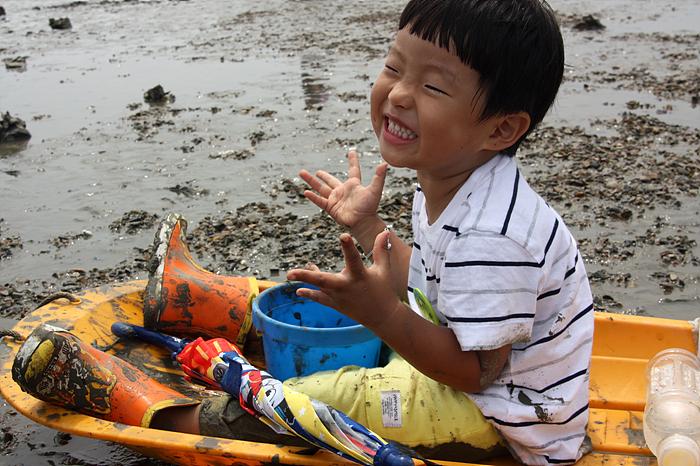 갯벌 위 썰매에 앉아있는 아이의 모습