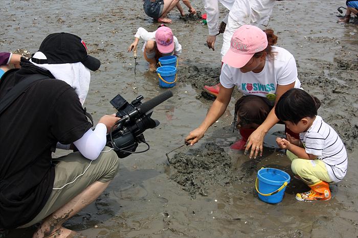갯벌체험을 하는 엄마와 아이의 모습을 찍는 카메라
