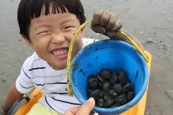 파란통 안에 담긴 것을 보여주면서 웃는 아이