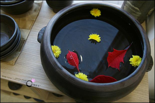 물을 받아놓은 항아리에 띄워놓은 꽃잎과 나뭇잎