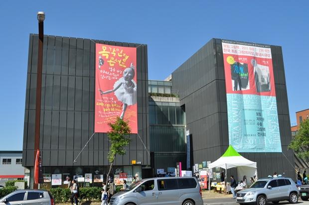 마리오네트 목각인형 콘서트 현수막이 건물에 걸려있다.