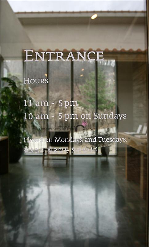 ENTRANCE HOURS 11an-5pm, 10am-5pm on Sundays 라고 쓰여진 유리