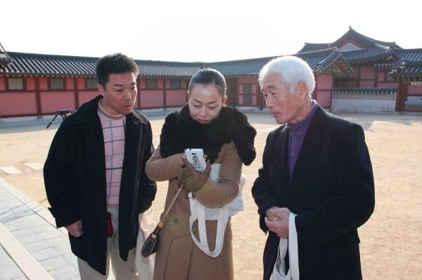 수원화성 어플을 이용해 설명을 듣고있는 일본인 관광객의 모습