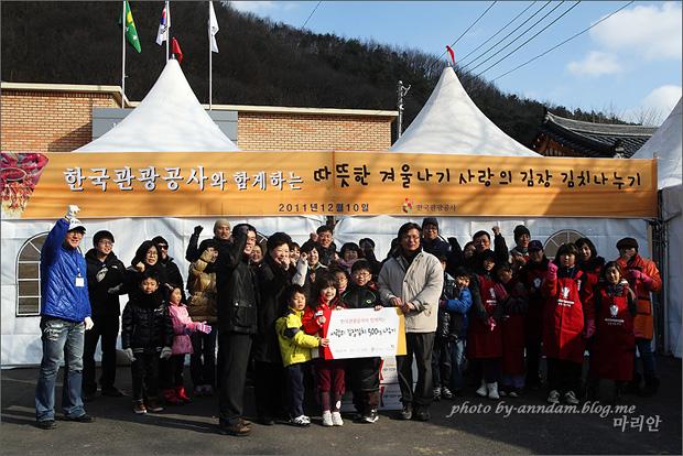 한국관광공사와 함께하는 따뜻한 겨울나기 사랑의 김장 김치나누기 현수막 앞에서 사진을 찍는 모습