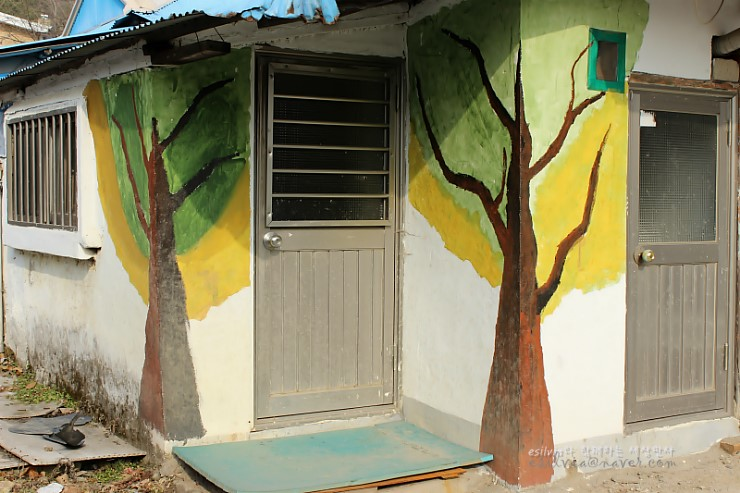 철문 양 옆으로 그려진 나무벽화