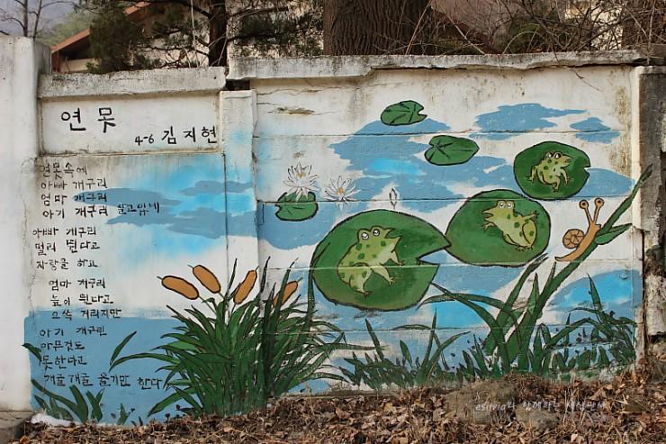 연못 4-6 김지현의 시 벽화. 연못속에 아빠 개구리 엄마개구리 아기 개구리 살고있네. 아빠 개구리 멀리 띈다고 자랑을 하고 엄마 개구리 높이 띈다고 으쓱 거리지만 아기 개구리 아무것도 못한다고 개굴개굴 울기만 한다.