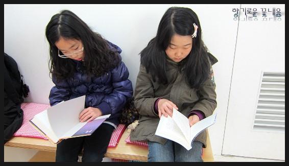 앉아서 책을 읽는 아이들의 모습