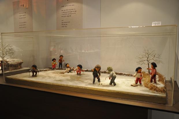 얼음판 위에서 썰매타기, 팽이치기 하는 아이들의 모습 인형