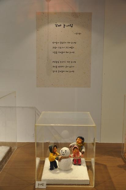 꼬마눈사람 시가 벽에 붙어있고 그 앞에는 눈사람을 만드는 아이들 모습의 인형이 전시되어 있다.