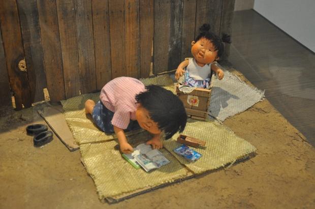 바닥에 포대를 깔고 책을 보는 아이의 모습