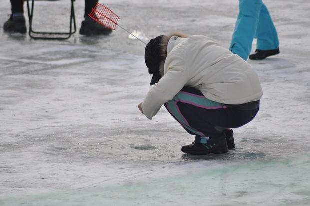 낚시대를 넣고 얼음구멍 안을 지켜보는 모습