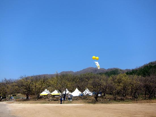 멀리 하늘에 떠있는 두개의 노란풍선과 현수막