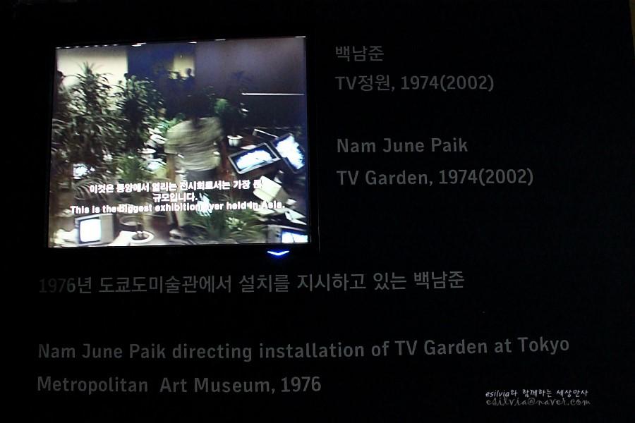 도쿄도 미술과에서 설치를 지시하고 있는 백남준의 모습이 나오는 스크린