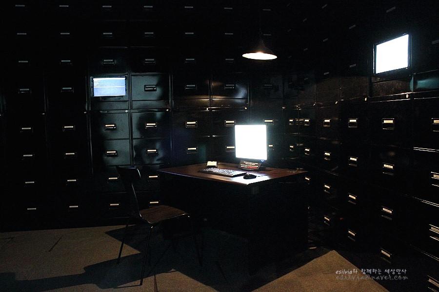 사방에 가득찬 서랍 상자와 책상위의 모니터가 있는 파일룸이라는 작품