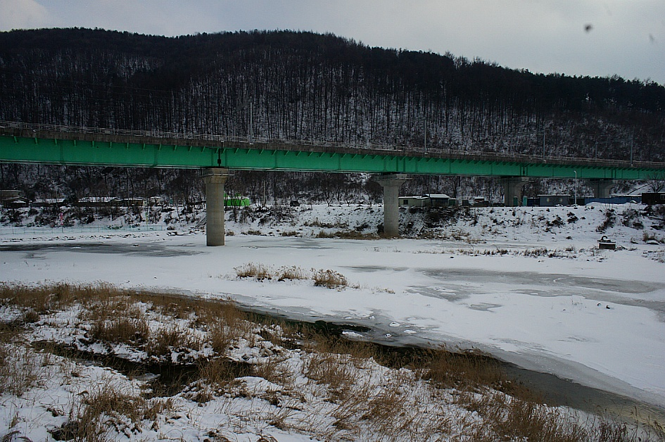 얼어붙은 강변과 그 위에 세워진 철로의 모습