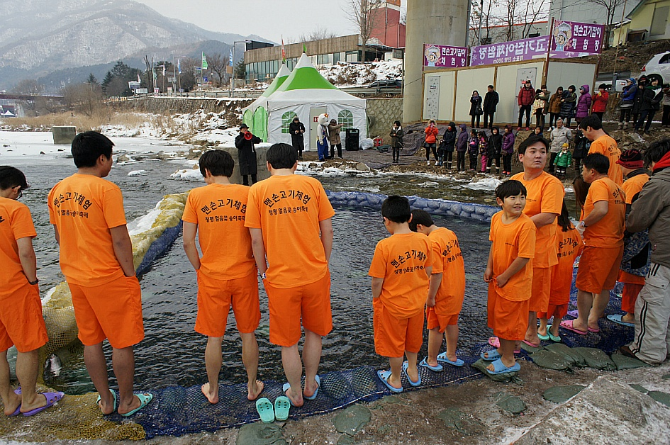 주황색 반팔 반바지를 입은 맨손송어잡이 체험 참가자들의 모습