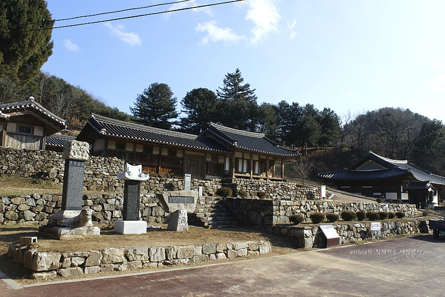 한옥건물과  그 앞에 서 있는 비석의 모습