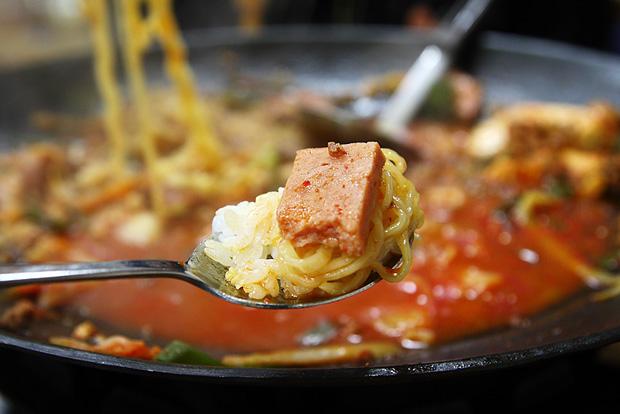 수저 위에 밥과 라면과 햄을 올린 모습