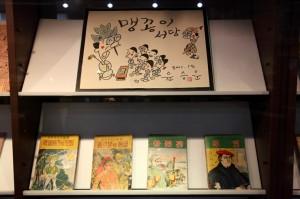 맹꽁이 서당그림이 그려진 액자아래 진열되어 있는 만화책의 모습
