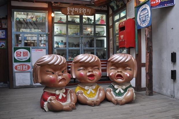 옛날 물건과 가판대 등이 있는 곳에 각기 다른 표정을 짓고 있는 여자 아이의 인형