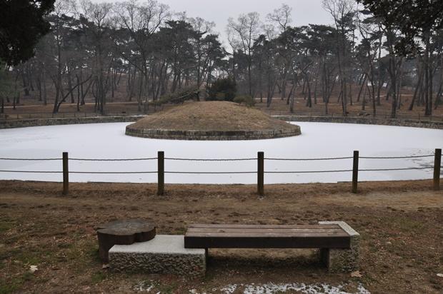 동그란 연못과 그 가운데 무덤 같이 생긴 언덕의 모습
