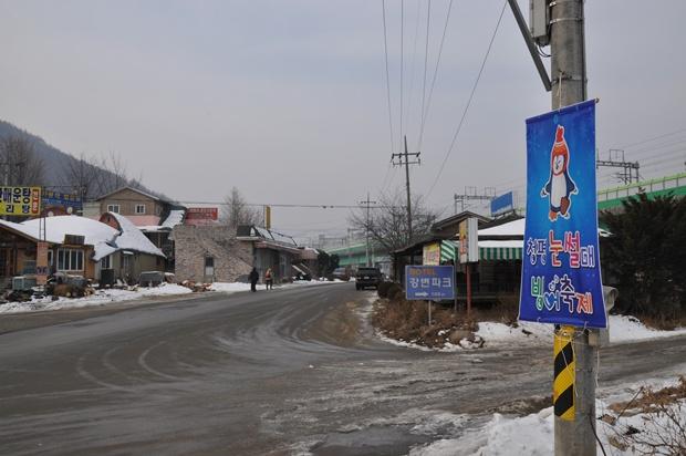 전봇대에 걸려 있는 눈썰매 빙어축제에 관한 현수막