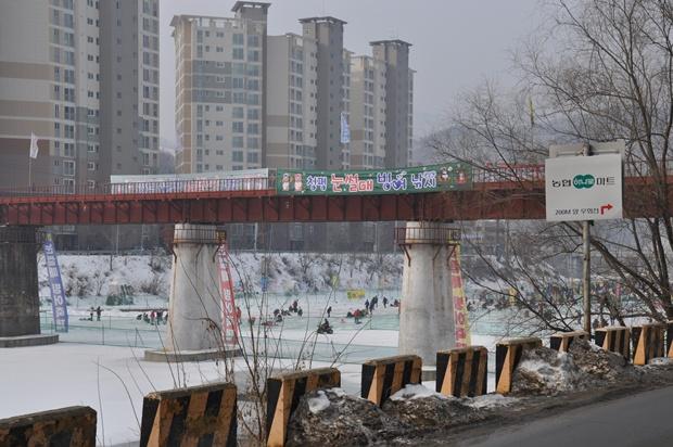 붉은 다리 밑 하천에 마련된 썰매빙어축제장의 모습
