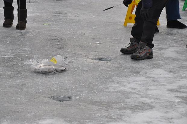 얼음에 뚫린 구멍과 얼음위에 놓인 잡은 송어