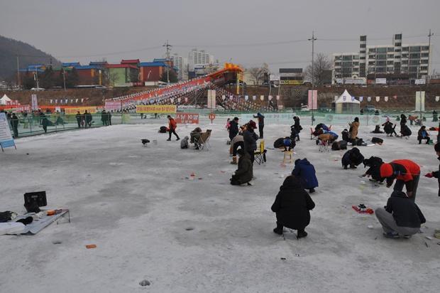 얼음에 구멍을 뚫고 빙어 낚시에 열중하는 사람들
