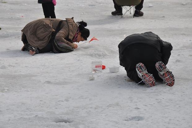 무릎을 꿇고 빙어 구멍을 보고 있는 사람들