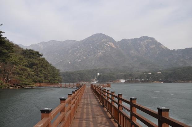 호수 위로 나 있는 다리와 멀리 보이는 산의 모습
