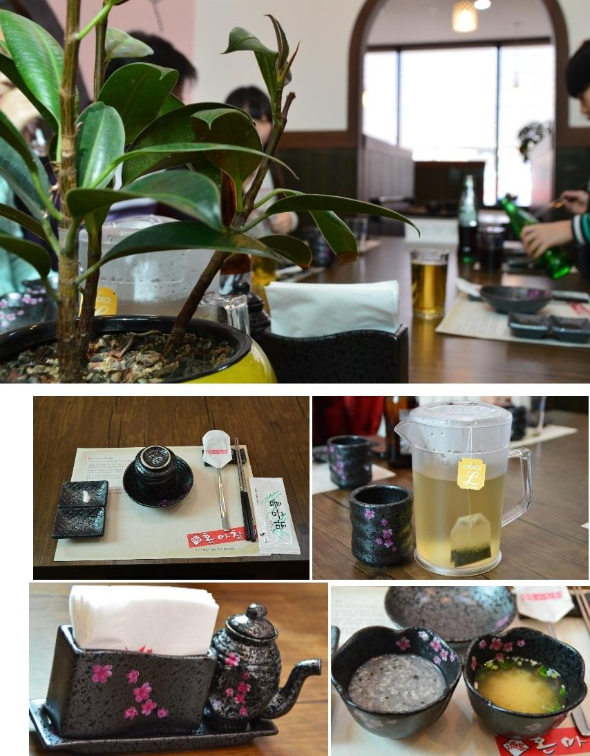 화분이 올려져 있는 테이블과 손님의 모습, 티백이 들어 있는 물통, 꽃무늬 그릇에 담겨 있는 죽과 국, 꽃무늬가 그려져 있는 휴지가 들어 있는 통, 테이블에 세팅되어 있는 컵 및 수저