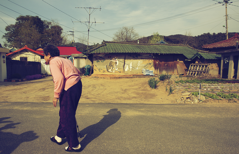 벽화가 그려져 있는 건물 옆 도로를 걸어가고 있는 할머니