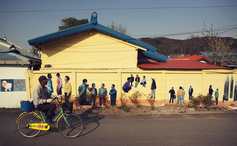 사람들이 그림이 그려져 있는 건물 옆으로 자전거를 타고 가는 사람의 모습