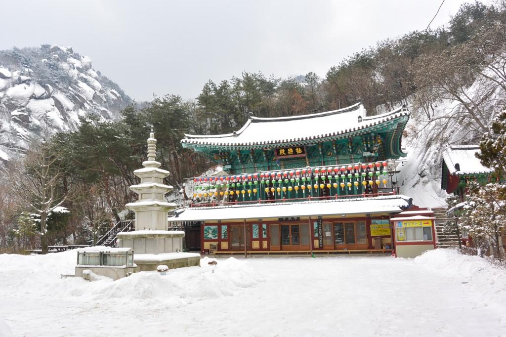 눈이 쌓인 호암사 사찰과 그 앞의 석탑의 모습