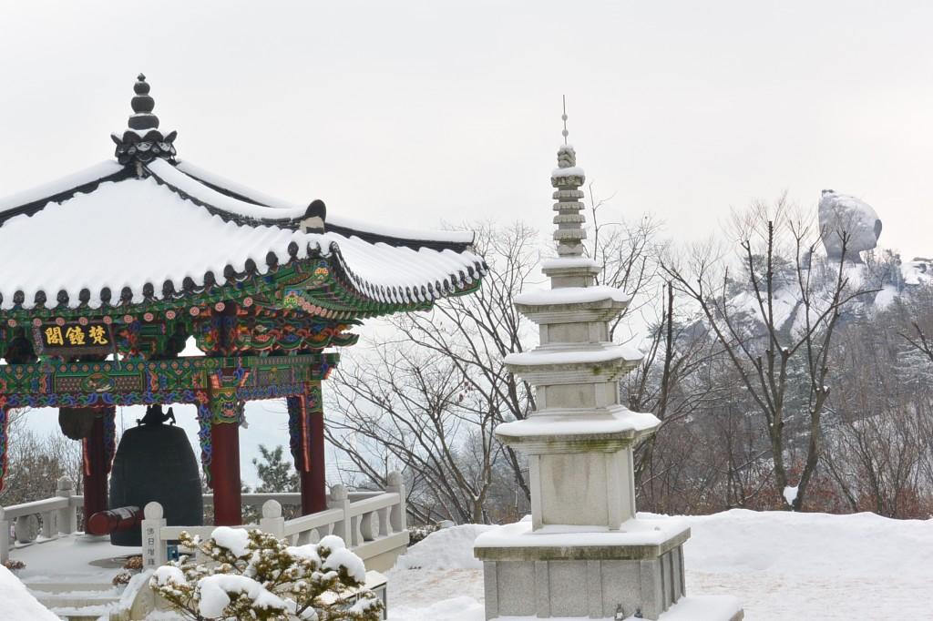 범종이 있는 정자와 그 앞의 석탑의 모습