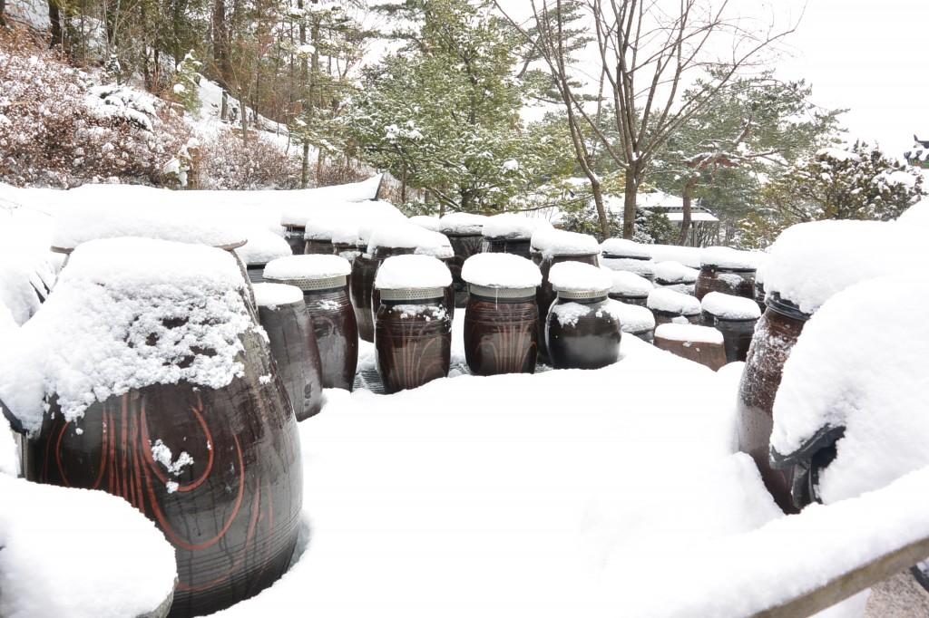 뚜껑에 눈이 쌓여 있는 장독대의 모습