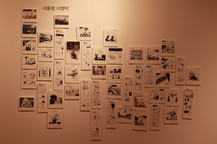 벽면에 걸려 있는 이명박 대통령에 대한 만화들