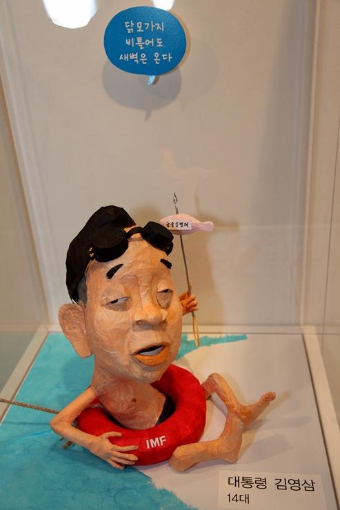 IMF라고 적힌 튜브를 타고 있는 김영상 대통령의 조형물