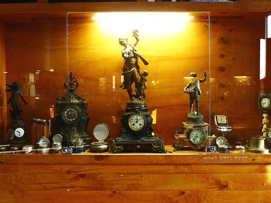 다양한 장식이 되어 있는 탁상시계를 비롯한 여러 시계들이 진열되어 있는 모습