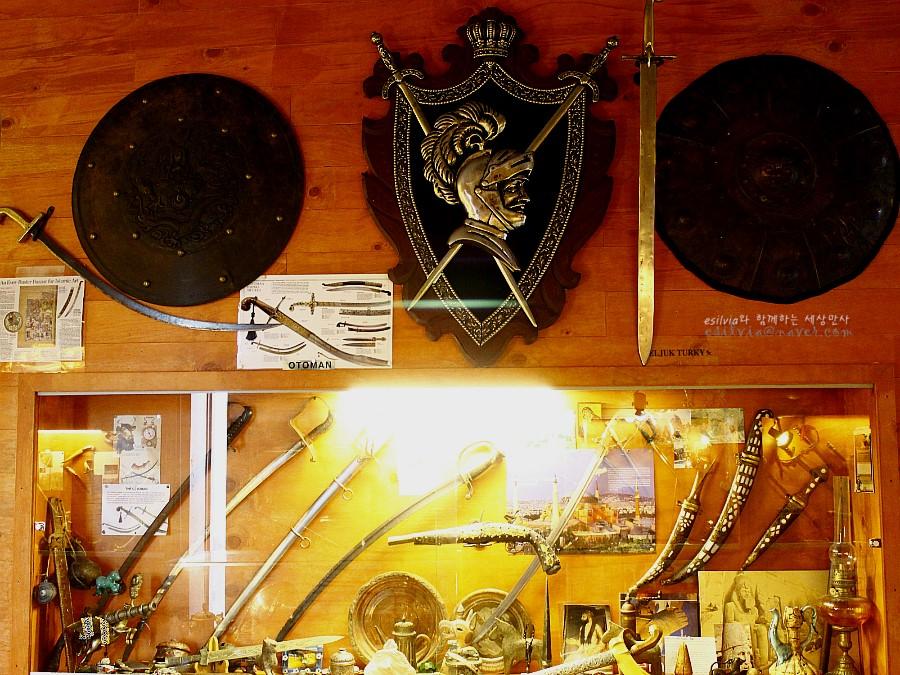 다양한 칼과 방패가 전시되어 있는 모습