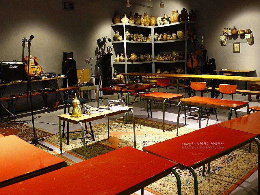 스피커와 기타 그리고 한 쪽 벽면에 지열되어 있는 도자기들이 있는 공간