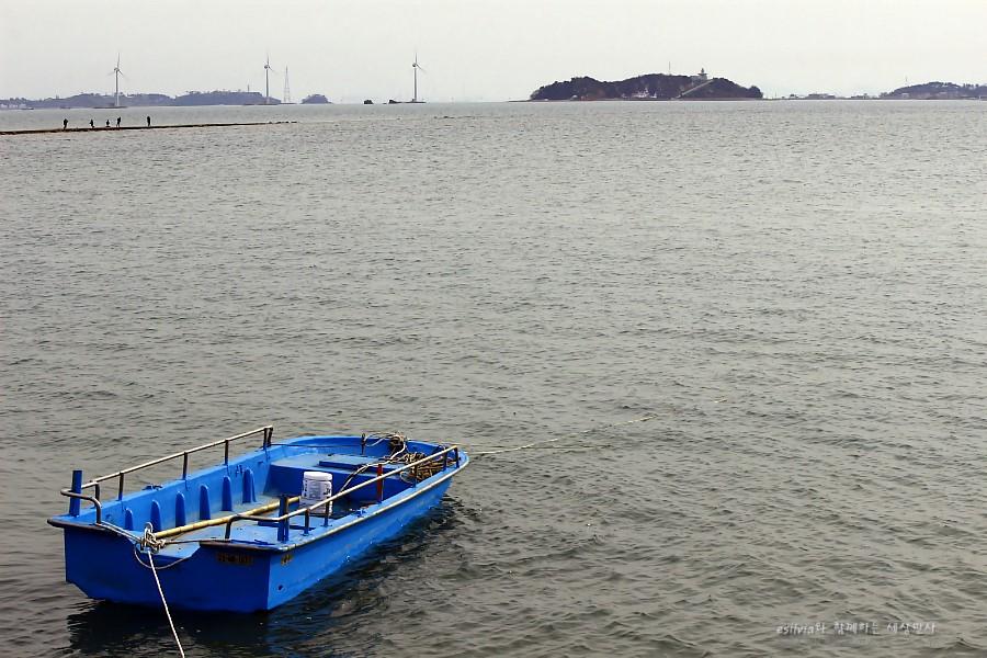 멀리 보이는 섬과 바다에 떠 있는 나룻배의 모습