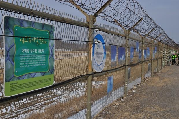 철조망에 설치되어 있는 평화와 생태를 주제로 진행한 대학생 공모전 당선작들의 모습