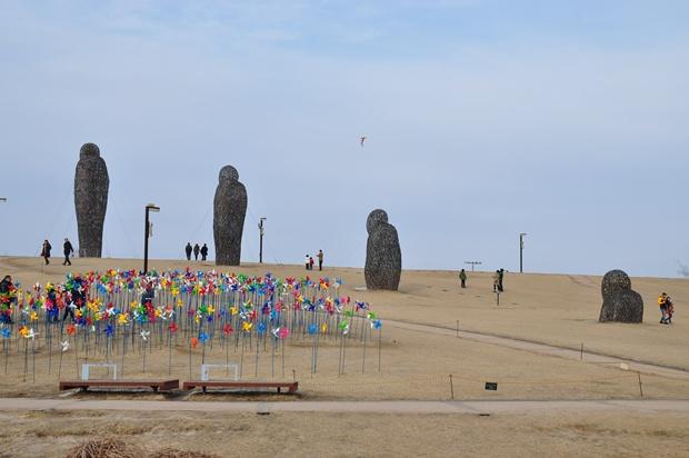 많은 바람개비와 커다란 조형물이 설치되어 있는 언덕의 모습