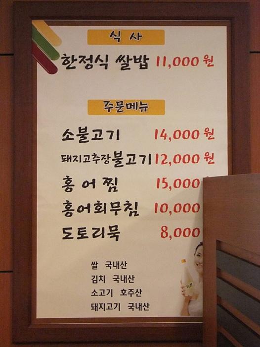 벽면에 걸려 있는 메뉴판, 식사 : 한정식쌀밥 11000원, 주문메뉴 : 소불고기 14000원, 돼지고추장불고기 12000원, 홍어찜 15000원, 홍어회무침 10000원, 도토리묵 8000원