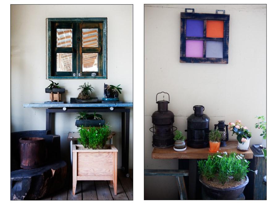 벽면에 걸린 가짜 창문과 깔끔한 인테리어의 모습, 테이블 위에 올려져 있는 등불과 화분들